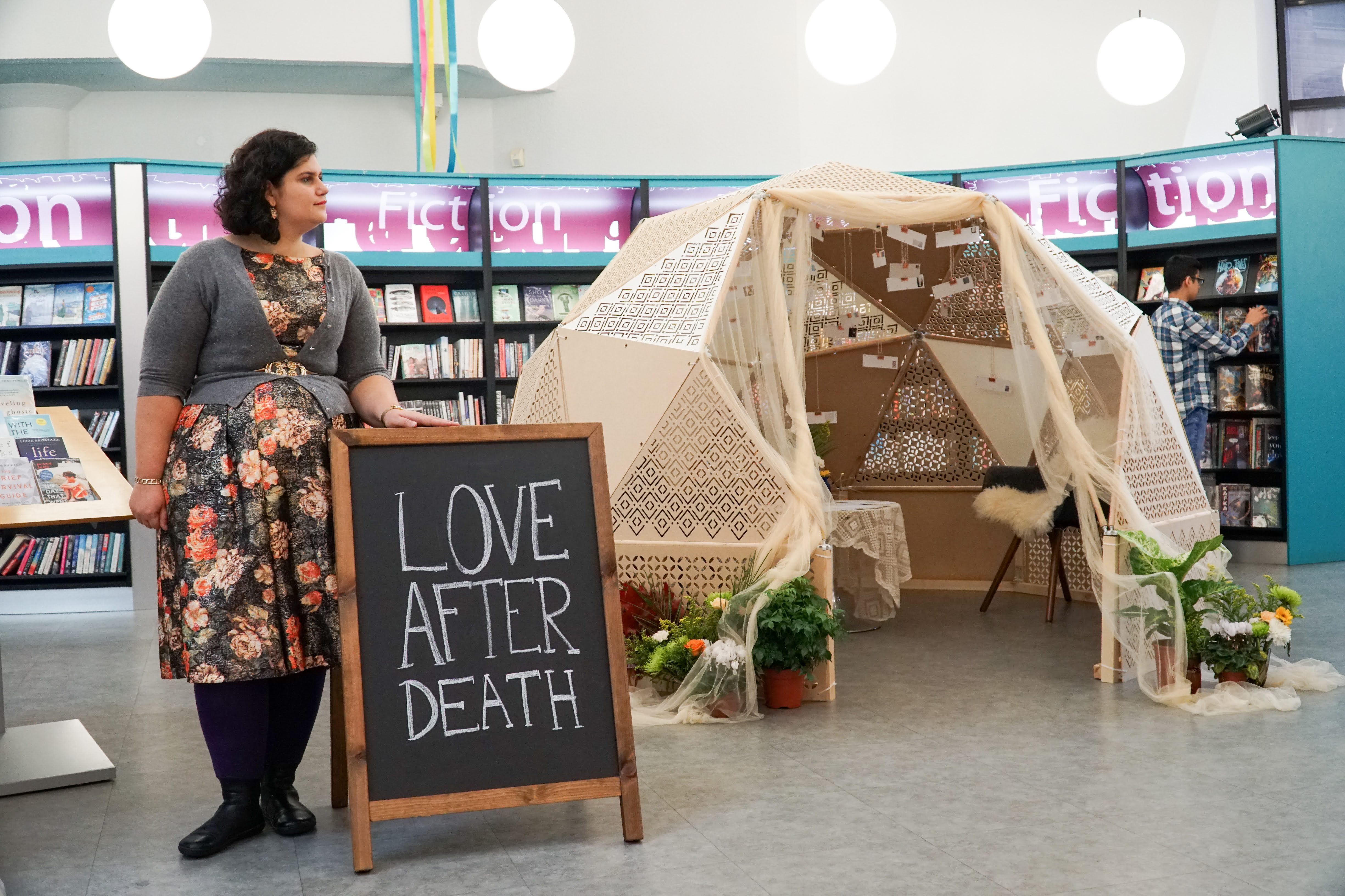 Woman next to chalkboard that says love after death