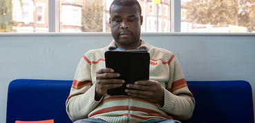 A man in a cream jumper reads from a tablet device.