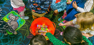 A circle of children play with toys in an orange bucket