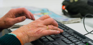 Elderly woman's hands on a keyboard