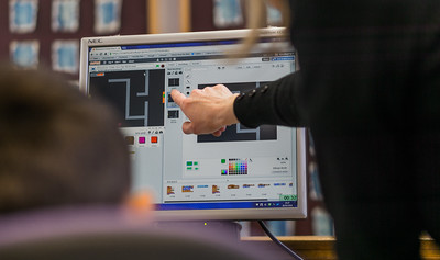 A finger points at a diagram on a computer screen