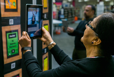 A woman holds up a tablet in front of her face in a library