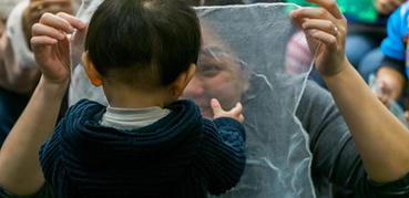 A woman smiles at a young child through gauze material
