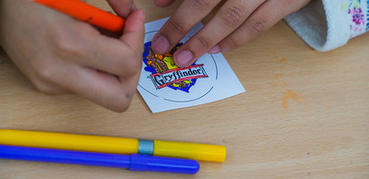 A child's hands draw on a sticker sitting on a wooden table