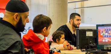 Two men help two young children with a computer activity