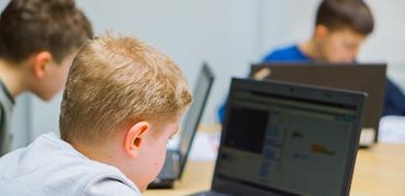 A boy studies a laptop screen.